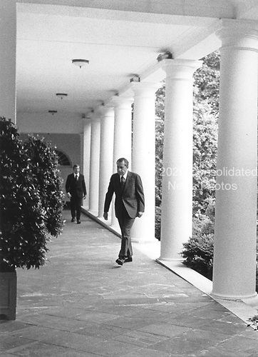 Washington, DC -- White House photo from 8 August, 1974 showing United States President Richard M. Nixon walking along the Colonnade at the White House prior to announcing his resignation..Credit: The White House / CNP
