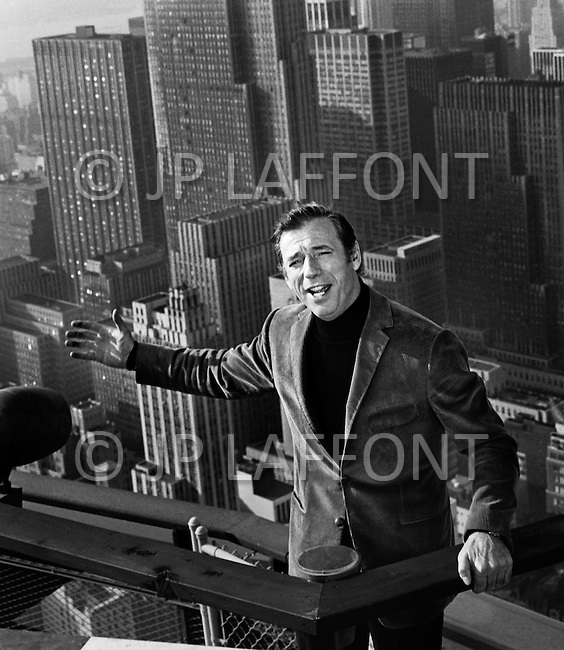 April 1969, Manhattan, New York, USA. Italian-born French actor and singer Yves Montand singing atop Manhattan's Pan Am Building, on the set of the movie On a Clear Day You Can See Forever directed by American Vincente Minnelli.
