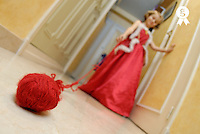 Girl (6-7) wearing red dress holding ball of red yarn, focus on yarn  (Licence this image exclusively with Getty: http://www.gettyimages.com/detail/200553548-001 )