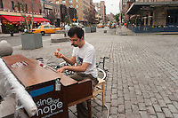 "New York, NY -  22 June 2010- A young man with a moustache plays ""Somewhere over the Rainbow"" with one hand while eating fresh strawberries with the other, in Gansvoort Plaza in the Meat Packing District of Manhattan... ""Play Me I'm Yours"" is a musical installation by British artist Luke Jerram who has been touring the project globally since 2008. From 9am-10pm each day, 60 pianos will be available to play across New York City. Presented by Sing for Hope they are located in public parks, streets and plazas the pianos will be available until 5th July for any member of the public to play and engage with."