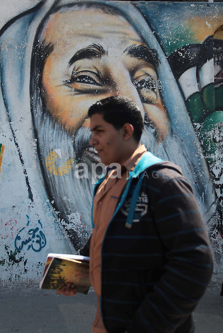 A Palestinian University student walks past a mural depicting late Hamas spiritual leader Sheikh Ahmed Yassin, marking the 10th anniversary of his death in Gaza City, March 22, 2014. Photo by Ashraf Amra