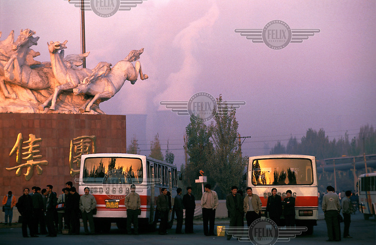 Mark Henley/Panos Pictures..China, Inner Mongolia, Baotou..Crowds. Industry. Pollution. People waiting for buses  going to work, by monumental statue with cooling towers of State-owned enterprise Baotou Iron and Steel Works rising behind.
