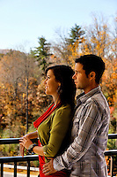 A man and woman look out over the Blue Ridge Mountains from a balcony in Asheville NC's Biltmore Park Town Square, a planned community of residential living, office spaces and shopping.