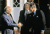United States President-elect George H.W. Bush, right, shakes hands with General Secretary Mikhail Gorbachev of the Union of Soviet Socialist Republics, left, as US President Ronald Reagan looks on, center, as they meet on Governor's Island in New York, New York on December 7, 1988.<br /> Credit: Arnie Sachs / CNP