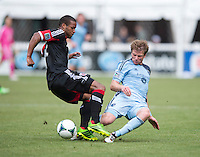 Jacob Peterson (37) of Sporting Kansas City slides into Ethan White (15) of D.C. United during a Major League Soccer match at RFK Stadium in Washington, DC.  D.C. United tied Sporting Kansas City, 1-1.
