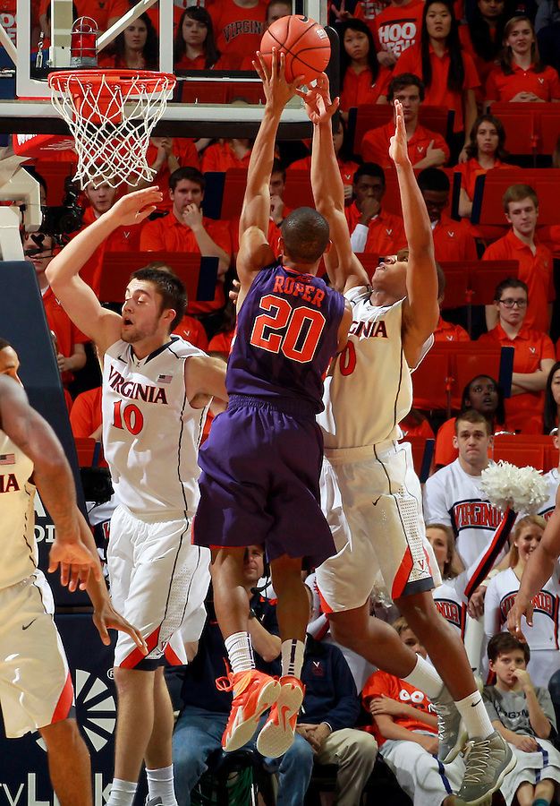 Virginia guard Devon Hall (0) blocks the ball of Clemson guard Jordan Roper (20) next to Virginia forward/center Mike Tobey (10) during an ACC basketball game Jan. 13, 2015 in Charlottesville, VA Virginia won 65-42.