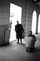Milano, corso Buenos Aires. Un mendicante in ginocchio sul marciapiede fa elemosina di fronte alle vetrine di un negozio Benetton --- Milan, Buenos Aires avenue. A beggar on his knees on the sidewalk in front of the windows of a store Benetton