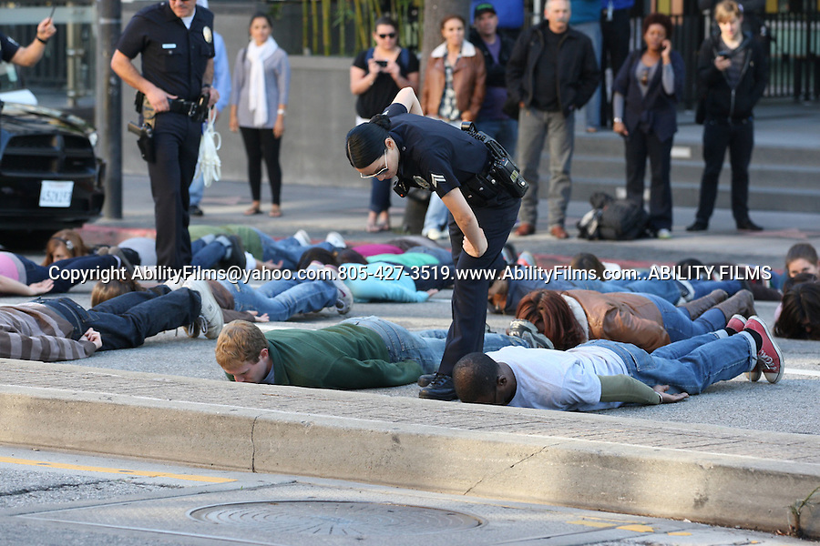 .January  9th  2012 Exclusive..Lucy Liu dressed as a police officer for the tv show Southland that was filming a protest scene on Hollywood Blvd. The protesters were laying face down on the ground. It's called planking.  Lucy was arresting them because they wouldn't move. Lucy was laughing with her crew members & security guard & adjusting her boot ..AbilityFilms@yahoo.com.805-427-3519.www.AbilityFilms.com