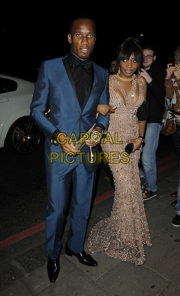 Didier Drogba & Alla Drogba.Attending the Didier Drogba Foundation Charity Ball, Dorchester Hotel, Park Lane, London, England, UK, .10th March 2012..full length blue suit black shirt  bow tie  beige beaded dress long maxi married husband wife .CAP/CAN.©Can Nguyen/Capital Pictures.