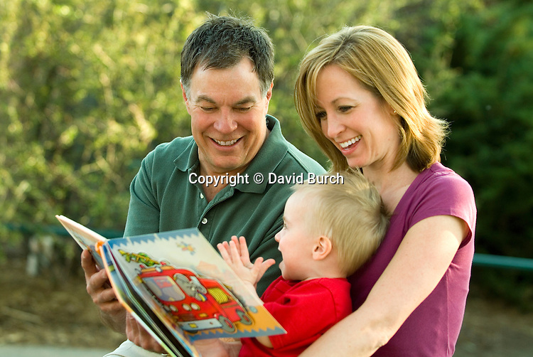 Father, daughter and grandson reading a book