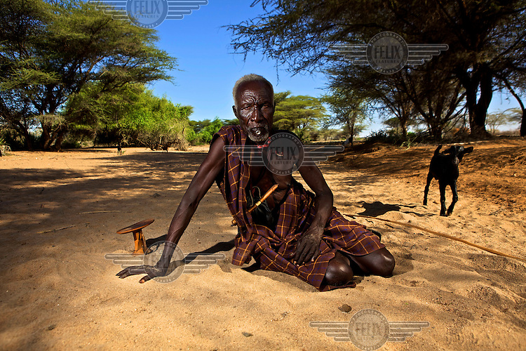 An elderly Turkana man rests in a dry river bed near the village of Kache Imeri. By his right hand is a small wooden head pillow. Northern Kenya is in the midst of a severe drought, and in the absence of safe drinking water and food, pastoral tribes are extremely vulnerable to disease and famine.