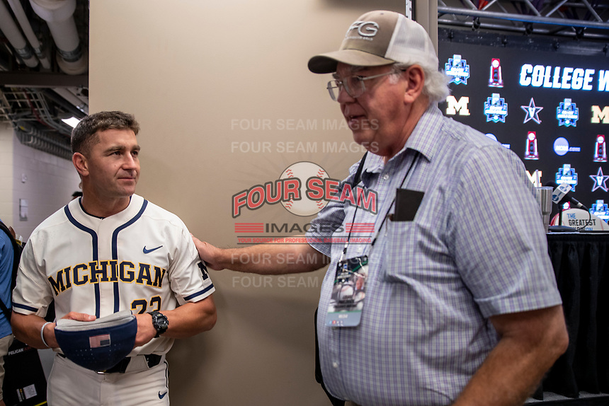 Michigan Wolverines head coach Erik Bakich answers questions from reporter Lou Pavlovich after the NCAA College World Series Finals press conference on June 23, 2019 at TD Ameritrade Park in Omaha, Nebraska. Michigan will play Vanderbilt in the CWS Finals. (Andrew Woolley/Four Seam Images)