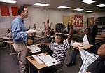 Oakland CA Students in 7th-8th grade geometry class demonstrating angle shapes with arms, being guided by teacher