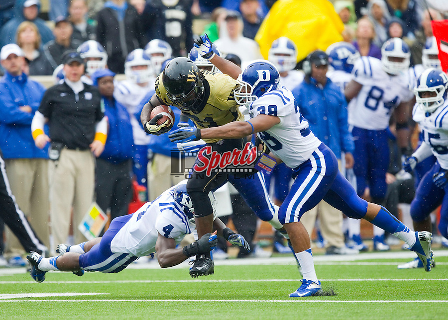 Deandre Martin (21) of the Wake Forest Demon Deacons is tackled by Walt Canty (4) and Jordon Byas (38) of the Duke Blue Devils at BB&T Field on September 29, 2012 in Winston-Salem, North Carolina.  The Blue Devils defeated the Demon Deacons 34-27.  (Brian Westerholt/Sports On Film)