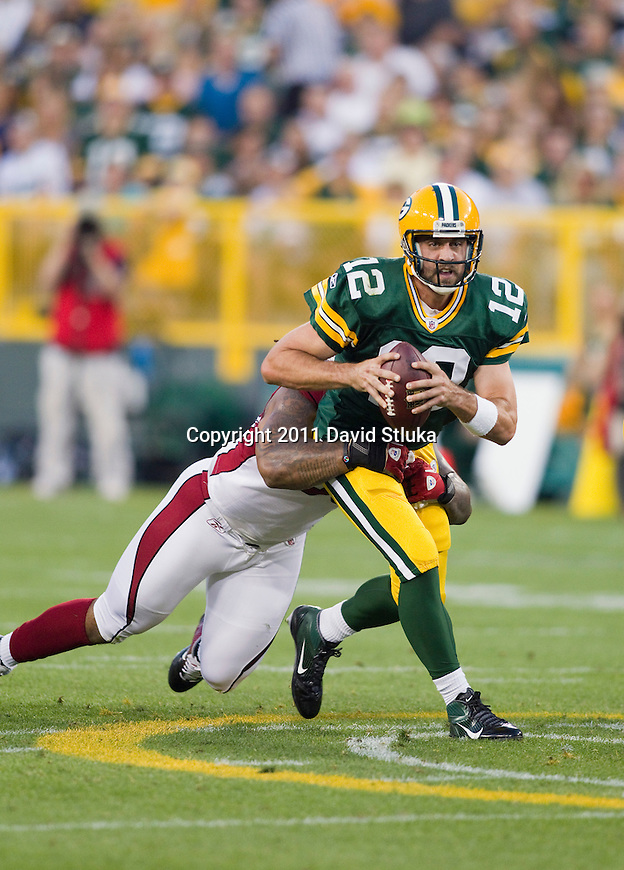 Green Bay Packers quarterback Aaron Rodgers (12) is sacked by Arizona Cardinals defensive lineman Darnell Dockett (90) during an NFL preseason football game on August 19, 2011 in Green Bay, Wisconsin. The Packers won 28-20. (AP Photo/David Stluka)