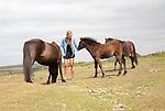 Woman with Dartmoor ponies, Dartmoor national park, Devon, England, UK