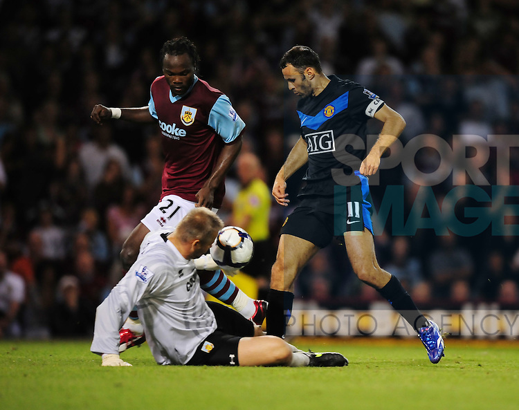 Brian Jensen of Burnley saves at the feet of Ryan Giggs of Manchester United