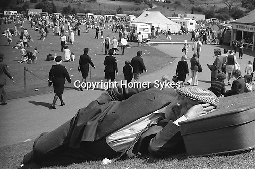 Middle aged miner asleep in the afternoon sun with his head rested on his suitcase, at the Durham annual Miners Gala. County Durham, England 1974. He is wearing his double breasted best suit, neck tie and flat cap for the occasion.