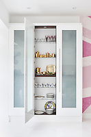 A glass-fronted cupboard against one wall of the kitchen displays glasses and a number of tea and coffee sets