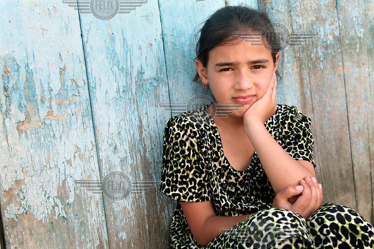 Zuhra, 10, sits outside her home in the village of Zimchurud.