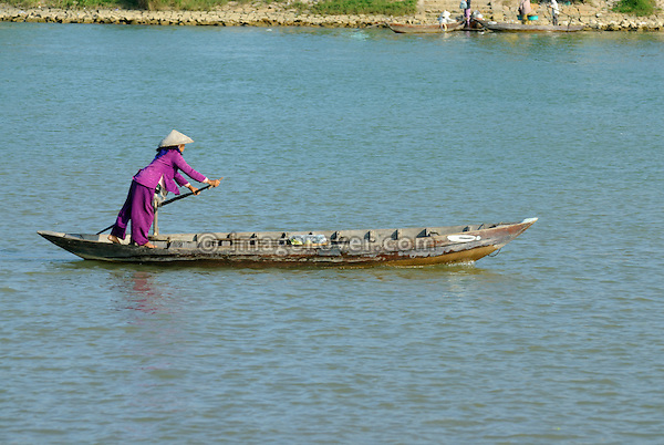 Asia, Vietnam, Hoi An. Vietnamese woman rowing her boat across the Thu Bon river near Hoi An.