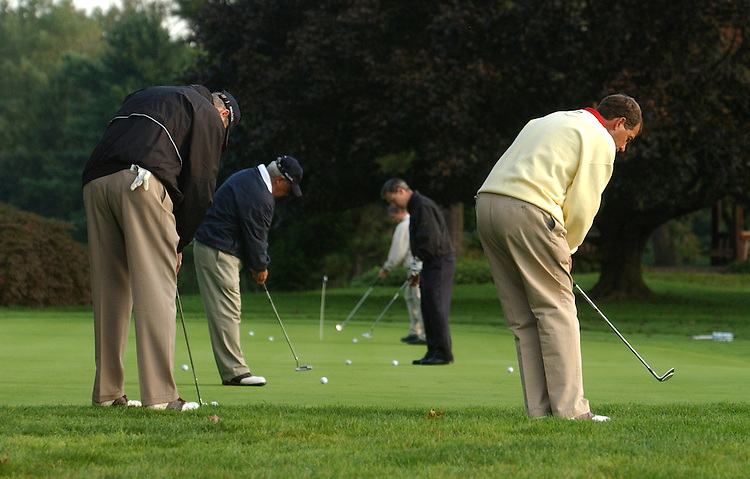 Reps. including John Boehner, R-Ohio, right, pratices putting before the First Tee Congressional Golf Tournament held at Columbia Country Club, Monday.