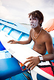 INDONESIA, Mentawai Islands, Kandui Surf Resort, young man with sunscreen on his face, smoking and holding his surfboard