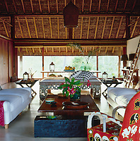 A large wooden coffee table and Balinese daybed are the central focus of the living room
