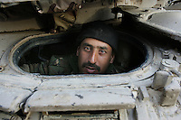 Iraqi tanker driver from the 1st company, 1st armour battalion of the 1st mechanized Iraqi Army Brigade helps the mechanics repair the transmission of a T 55 tank  while conducting  patrols, check points and observation posts on code name route Michigan, the main road of Ramadi in the week during the national election on TUE Dec 13 2005 in Ramadi, Iraq. 1st company is part of the first armor battalion of the New Iraqi Army. it has started its training in January 2005. after 50 days their 35 russian and chinese built T 55 tanks begun conducting operations under the guidance of a US military adivisor team. in April 2005 they patrolled in the Abu Ghraib area concluding their first significant mission. While these old tanks are rolling on the ramadi streets more modern T72s are getting ready to become fully operational in Taji, their main base. the Iraqi army wanted to show their power in ramadi during the Dec 15 elections displaying their new armour company. but like all the other Iraqi forces they are not going to secure the polling sites, staying in the rear with the rest of the iraqi and coalition forces. T 55s are very old tanks. production begun in the late 50s to the late 70s. athough obsolete many countries still use the T55 as their main heavy armoured combat vehicle. slow, heavvy and with very little room for the crew it suffers from many mechanical problems constantly challenging the iraqi mechanics and engineers.
