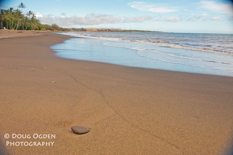 A lone stone on the black sands beach at Waimea, Kauai, Hawaii
