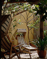 A pair of deckchairs with green and cream striped covers and topped with extravagant hoods are placed in a sheltered courtyard