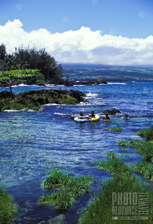 Children in a rubber raft float in the ocean near Hilo Bay, Hawaii