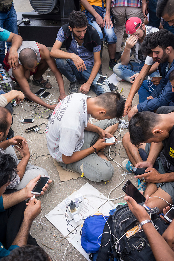 Refugees charging their phones to a power outlet connected to a generator. Refugees at Eidomeni, Greece Border crossing ( Greek side)