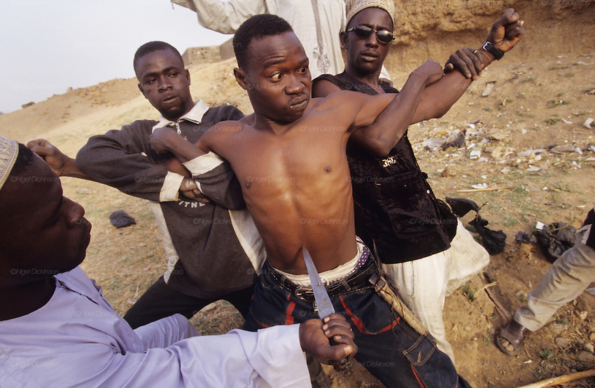 Gang members high on drugs play weird power games. Badawa Ghetto Street Gang on the outskirts of Kano. They are Muslim but drink alcohol, smoke and inject hard drugs..The implementation of Islamic Sharia Law across the twelve northern states of Nigeria, centres upon Kano, the largest Muslim Husa city, under the feudal, political and economic rule of the Emir of Kano. Islamic Sharia Law is enforced by official state apparatus including military and police, Islamic schools and education, plus various volunteer Militia groups supported financially and politically by the Emir and other business and political bodies. Fanatical Islamic Sharia religious traditions  are enforced by the Hispah Sharia police. Deliquancy is controlled by the Vigilantes volunteer Militia. Activities such as Animist Pagan Voodoo ceremonies, playing music, drinking and gambling, normally outlawed under Sharia law exist as many parts of the rural and urban areas are controlled by local Mafia, ghetto gangs and rural hunters. The fight for control is never ending between the Emir, government forces, the Mafia and independent militias and gangs. This is fueled by rising petrol costs, and that 70% of the population live below the poverty line. Kano, Kano State, Northern Nigeria, Africa