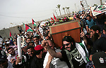 Palestinians chant slogans while carrying the coffin of Italian activist Vittorio Arrigoni, age 36, as they transfer it through Rafah border crossing in southern Gaza Strip, Monday, April 18, 2011. Gaza's Hamas government said Monday it was searching for three suspects in last week's killing of Arrigoni, an Italian activist. Hamas has been conducting a manhunt since Arrigoni's death who had been assisting local Palestinians in Gaza. The 36-year-old's body was found early Friday, hours after a video showing him beaten and blindfolded surfaced on the Internet. Photo by Mohammed Othman