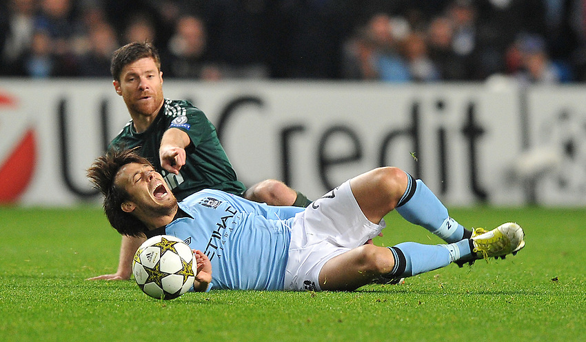 Manchester City's David Silva  is tackled by Real Madrid's Xabi Alonso ..Football - UEFA Champions League Group D - Manchester City v Real Madrid  - Wednesday 21st November 2012 - Etihad Stadium - Manchester..