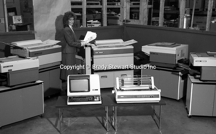 Pittsburgh PA: Saleswoman demonstrating the new copiers and computer systems for a brochure.  The New DECMate computer and line printer on display - 1980