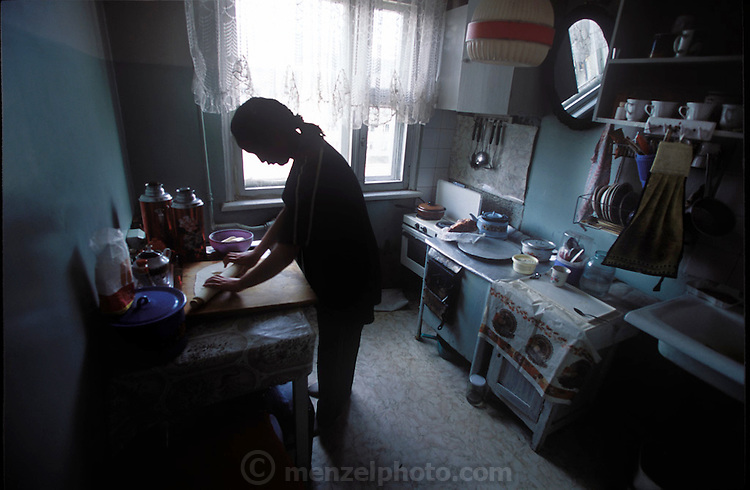 (MODEL RELEASED IMAGE). Khorloo rolls out dough for her family's dinner of buuz (mutton-stuffed dumplings) in the small kitchen of her Mongolian home which her family of four shares with two other families. (Supporting image from the project Hungry Planet: What the World Eats.)