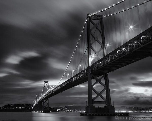 Black and white of San Francisco's Bay Bridge in the early morning as the clouds move