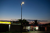 Eine Abendszene an der Hauptstraße in Neum, Bosnien. / A night scene at the mainroad of the citiy of Neum, Bosnia.<br />Der kleine Ort Neum liegt in Bosnien-Herzegovina und bildet den einzigen Zugang zum Meer des Balkanlandes. Auf einer Länge von 9 km durchschneidet der Ort das kroatische Staatsgebiet (Neum-Korridor) Seit dem EU-Beitritt Kroatiens ist Neum auf beiden Seiten von EU-Außengrenzen eingeschlossen. / The small city of Neum in Bosnia and Herzegovina is the only place in Bosnia, where the country has access to the adriatic sea. Over a length of 9 kilometers the area cuts Croatian territory in two pieces. Since Croatia became part of the European Union, the city of Neum is enclosed between two EU-boarders.