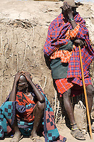 Two Masai men take a rest outside a hut in their village near the Serengeti National Park, Tanzania.