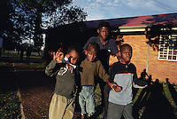 KLIPRIVER, SOUTH AFRICA APRIL 14: Johannes Mcede, age 17, walks Kabelo Claries, age 7, .Tshepo Raphiri, age 10, Lungisane Ngcaweni, age 10, early in the morning to have breakfast at Sibonile (means: we have seen) School for the Blind on April 14, 2003 in Klipriver, south of Johannesburg, South Africa. A blind woman founded the school in 1994. The school has about 125 students from disadvantaged communities around South Africa. Many of the children have faced rejection from their families and communities, and at Sibonile they have a chance for a good education. (Photo: Per-Anders Pettersson)...