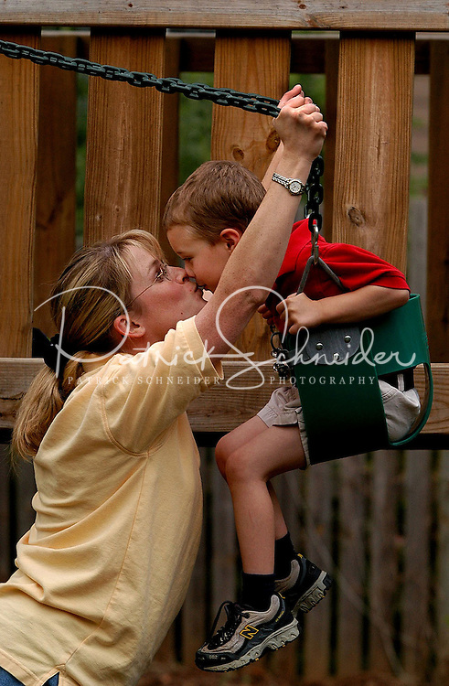A young mother makes her son pay the ?kissy toll? before she starts pushing him on the swing on their backyard play set.