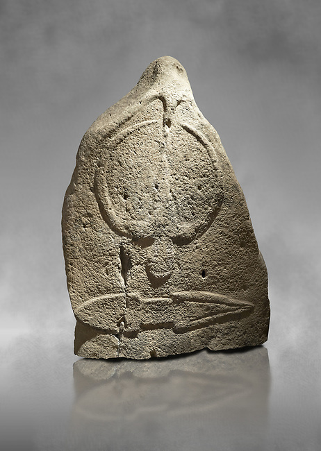 Late European Neolithic prehistoric Menhir standing stone with carvings on its face side. The representation of a stylalised male figure starts at the top with a long nose from which 2 eyebrows arch around the top of the stone. below this is a carving of a falling figure with head at the bottom and 2 curved arms encircling a body above. at the bottom is a carving of a dagger running horizontally across the menhir.  From Barrili I site, Laconi. Menhir Museum, Museo della Statuaria Prehistorica in Sardegna, Museum of Prehoistoric Sardinian Statues, Palazzo Aymerich, Laconi, Sardinia, Italy