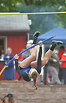 A pole vaulter on her way over the bar.
