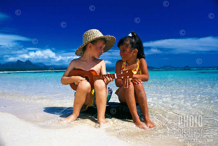 Boy in straw hat plays ukulele for young girl at the beach. Kailua, Oahu.