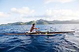 FRENCH POLYNESIA, Tahaa Island. Roe, riding his outrigger canoe between Tahaa Island and Vahine Island. Tahaa Island can be seen in the background.