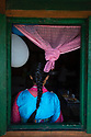 India - Sikkim - A young Lepcha woman stands in the window frame of her house in a village located on into the jungle.