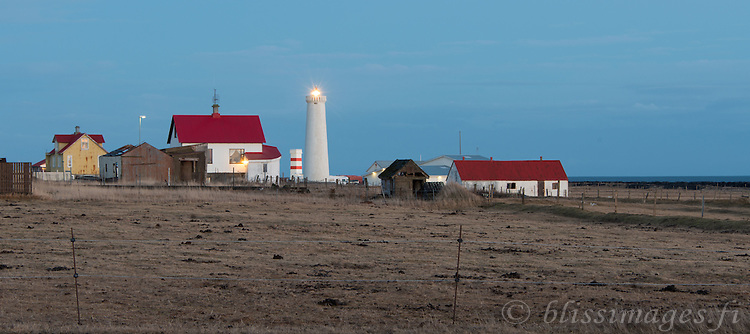 Garðskagi Light shines at dusk from the northernmost tip of the Reykjanes Peninsula, 50 km from Reykjavik, Iceland in the North Atlantic.