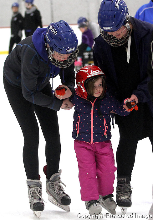 Braintree High School girl's hockey team members Hannah Fenton (L) and Olivia Finn (R) skates with Fiona Hyland (center) at the Braintree High School girl's hockey team annual learn to skate program at Shea Memorial Rink in Quincy on Sunday, Feb. 22, 2015.(Photo by Gary Wilcox)